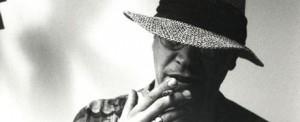 Homem com chapeu e cigarro