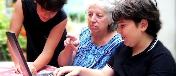Senhora ao notebook ajudada por dois garotos