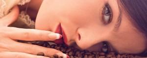 Rosto feminino deitado sobre grãos de café