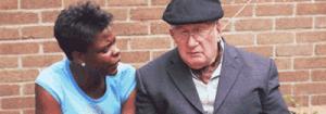 Mulher mais nova e homem mais velho sentados em banco