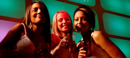 3 mulheres rindo e brindando