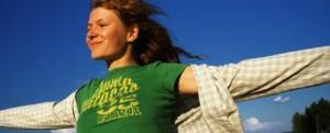 uma jovem mulher com um leve sorriso no rosto, os braços abertos e vento nos cabelos