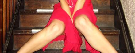 Mulher sentada em escada com as pernas fechadas