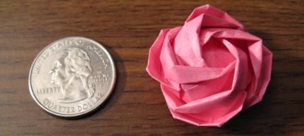 Mesa com uma moeda e uma rosa de papel