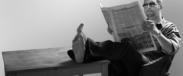 homem lendo jornal com o pe em cima da mesa