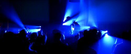 Pessoas dançando em uma balada com luz azul