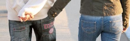 Casal andando com a mão da moça no bolso traseiro da calça do rapaz