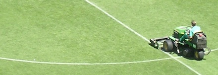 Carrinho aparando grama de campo de futebol