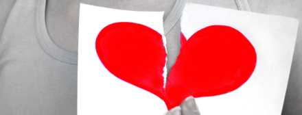 Coração partido ao meio segurado por uma mulher