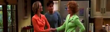 Duas mulheres se cumprimentando e um homem olhando