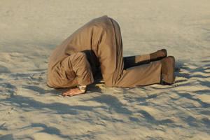 homem com a cabeça enterrada na areia