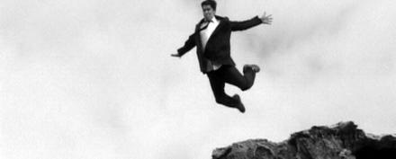 Homem de terno pulando de um lugar alto