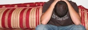 Homem sentado no sofá com cabeça para baixo e mãos em cima da cabeça