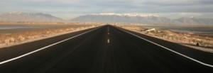 uma estrada reta com uma montanha na frente
