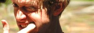 Homem com dedo na boca